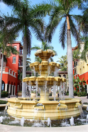 a large stone water fountain stands in the center of two colorful shopping mall buildings and some tropical Palm Trees Imagens