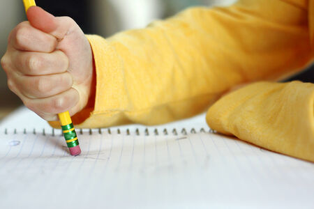deleting: a child has made a mistake while writing and is holding a pencil and erasing on white notebook paper
