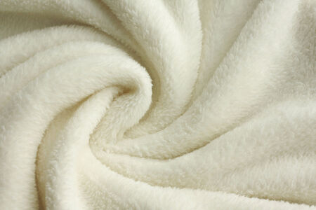 a warm, white, plush micro fleece blanket is swirled into a cirular pattern background