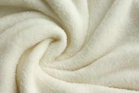 a warm, white, plush micro fleece blanket is swirled into a cirular pattern background