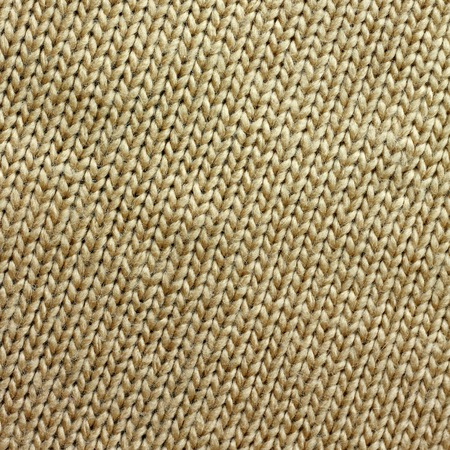 a square background of tweed tan or camel colored knit fabric is braided in lines Фото со стока