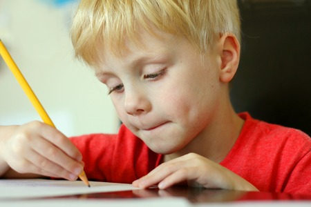 school desk: a young, preschool aged child is drawing on a white piece of paper with a writing pencil