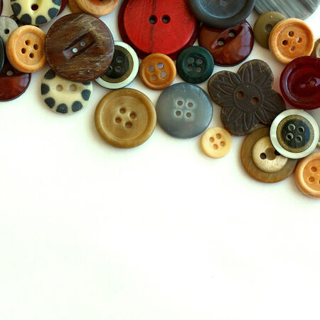 art supplies: a collection of natural colored vintage sewing buttons are scattered as a top border, isolated on a white background with copyspace