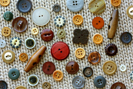 brown, tan, and natural colored collection of vintage sewing buttons scattered on a tweed knitted fabric background photo