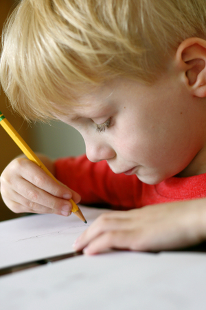 person writing: a young, preschool aged child is drawing on a white piece of paper with a writing pencil