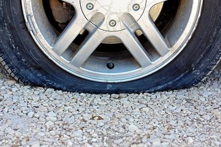 A, 비포장 도로에 튀어있는 평면 자동차 타이어의 중심 뷰를 닫습니다. 복사 - 공간에 대 한 방입니다. 스톡 콘텐츠