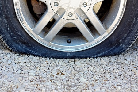 flat tire: a close up, centered view of a flat car tire that has popped on a gravel road.  Room for copy-space. Stock Photo