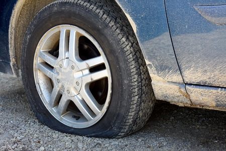 close up on the flat tire of a dirty old blue car stranded on a gravel road Stock Photo