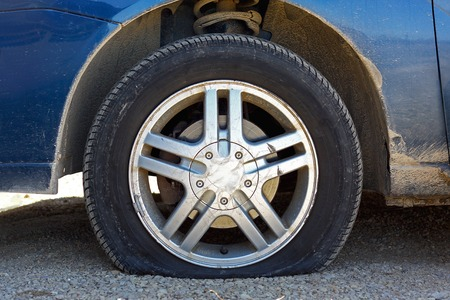 close up of a flat tire of a blue car centered on gravel road