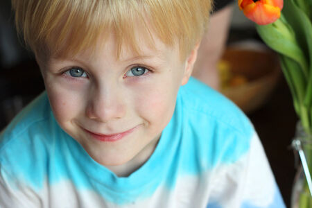 head and shoulders portrait of a sweet young child at home, smiling peacefully