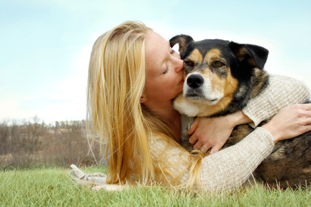 a young caucasian woman with long blonde hair is laying outside hugging and kissing her German Shepherd Dog