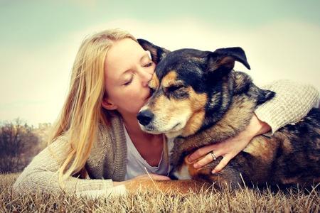 een jonge vrouw en haar Duitse herder hond zijn buiten tot in het gras, en ze is liefdevol knuffelen en zoenen hem vintage stijl kleur Stockfoto