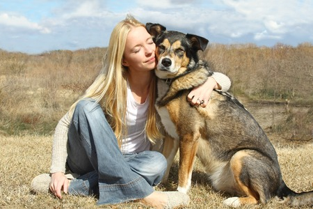 a special and serene moment as a happy woman with her eyes closed is lovingly hugging her large German Shepherd dog outside