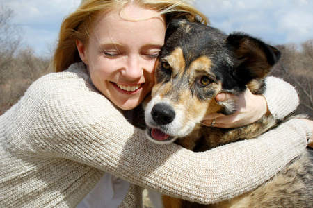 a loving and candid portrait of a happy woman hugging her large German Shepherd dog  写真素材