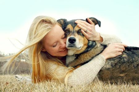 eine junge Frau kaukasisch außerhalb Verlegung mit ihrem deutschen Schäferhund, umarmt ihn liebevoll Standard-Bild