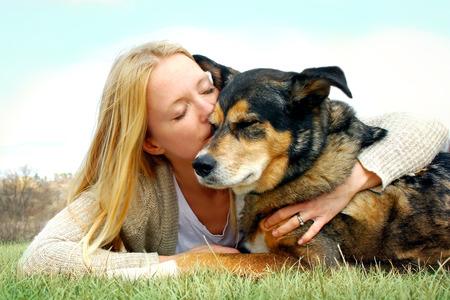 eine junge Frau und ihr deutscher Schäferhund außerhalb der in das Gras, und sie ist liebevoll umarmen und ihn zu küssen