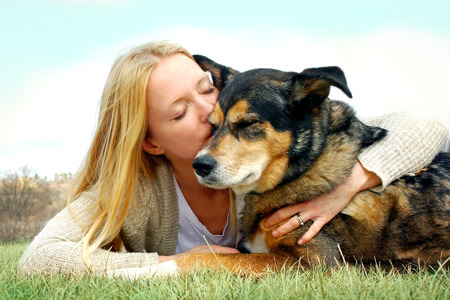 a young woman and her German Shepherd dog are laying outside in the grass, and she is lovingly hugging and kissing him