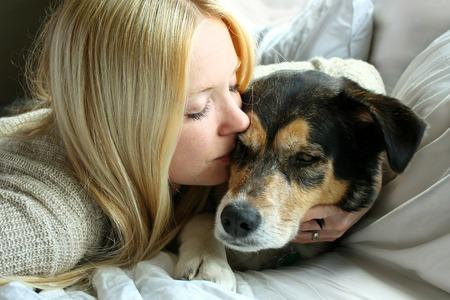 여자가 사랑스럽게 그를 포옹하고 그의 모피를 안고, 그녀의 독일 셰퍼드 강아지와 함께 누워있다
