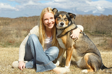 a happy, smiling young woman and her large German Shepherd Dog are sitting outside in the country, hugging  photo