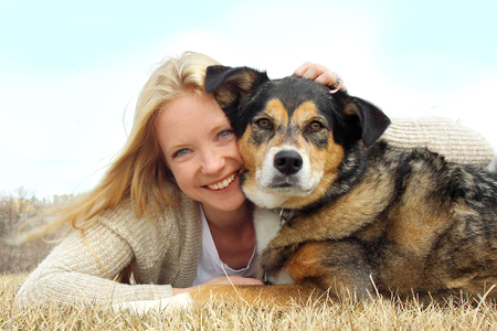 a happy young woman and her German Shepherd dog are laying on the grass outside hugging