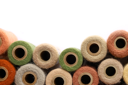 a collection of natural colored antique yarn spools a framing a white background Stock Photo - 27713359