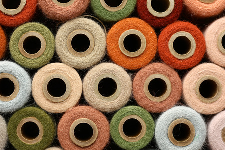 an antique yarn spool collection is stacked together to create a colorful abstract circle background