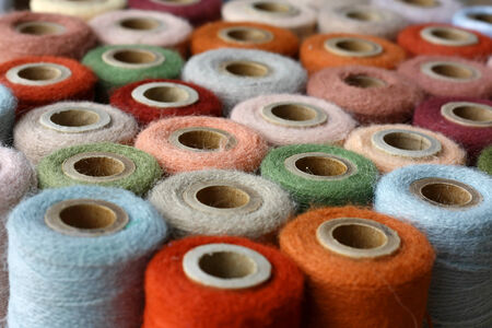 A collection of natural colored vintage thread spools are gathered together.  Shallow depth of field. Stok Fotoğraf