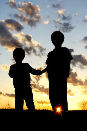 een silhouet van twee jonge kinderen; een kleine jongen en zijn broertje, liefdevol hand in hand in de voorkant van een prachtige zonsondergang in de hemel.