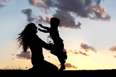 空の夕日の前に、抱擁を愛する母親の腕の中に実行している幸せな若い男の子子供のシルエット。 写真素材