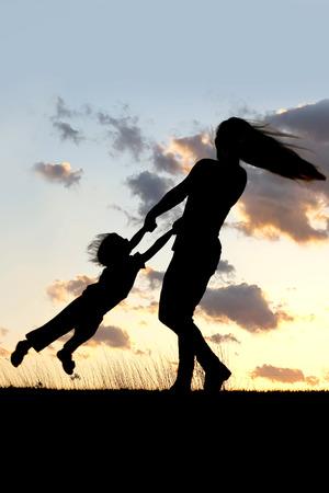 遊び心のある若い母親紡績および日没時外の彼女の小さな子供とダンスのシルエット。