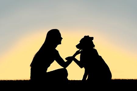 siluetas de animales: Una silueta de una chica sentada afuera, entrenar y jugar con su perro pastor alem�n, mientras estrecha la mano aislado en frente de una puesta de sol en el cielo. Foto de archivo