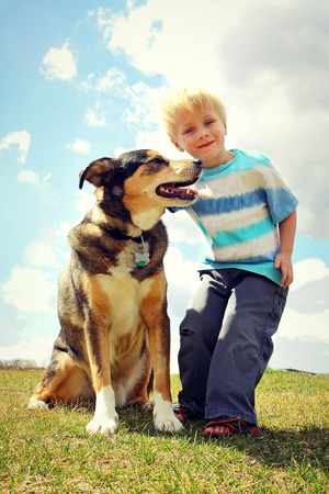 adopt: a portrait of a happy young kid playing outside with his large German Shepherd mix breed dog.
