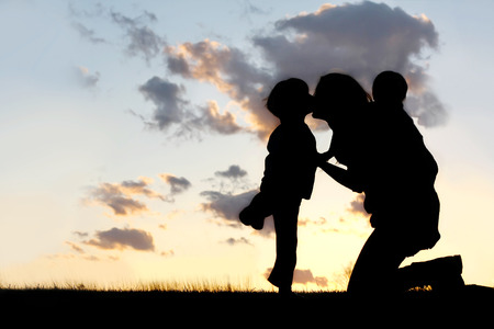 the Silhouette of a mother and her two young children; a little boy and his baby brother are playing outside at sunset, hugging and kissing. Stockfoto