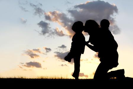bacio: Silhouette di una madre ei suoi due bambini; un piccolo ragazzo e suo fratello del bambino stanno giocando fuori al tramonto, abbracciare e baciare.