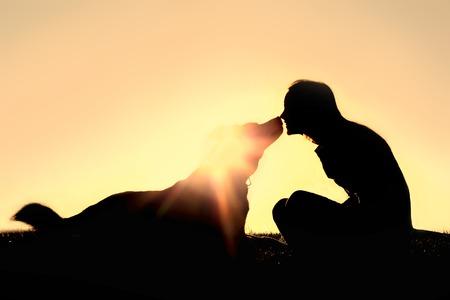 행복 한 젊은 여자의 실루엣이 사랑스럽게 그녀의 큰 독일 셰퍼드의 혼합 품종의 강아지 키스 일몰에 외부 앉아있다.