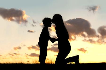 dia y noche: Silueta de una joven madre con amor besa a su peque�o hijo en la frente, en las afueras aislado en frente de una puesta de sol en el cielo.