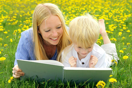 and four of the year: a happy mother is laying in the Dandelion flowers outside with her young child, reading him a story from a book. Stock Photo
