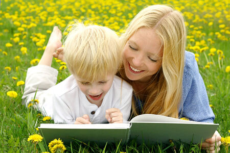 2 year old: a happy mother is laying in the Dandelion flowers outside with her young child, reading him a story from a book. Stock Photo