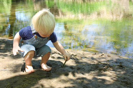 a young caucasian child is playing with a stick in the mud by a river in the woods