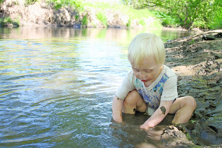 a young boy child is sitting in on the beach of a river in the woods, playing in the mud on a summer day. photo