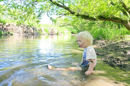 A Little toddler boy child is sitting down in a muddy river in the woods on a summer day  photo