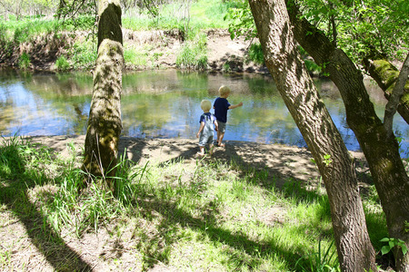 Two young children, a little boy and his baby brother are outside, playing in the mud by the river in the woods photo