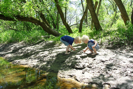 Two young children, a little boy and his baby brother are outside, playing in the mud by the river in the woods Stockfoto