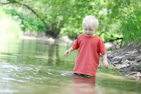 two year old: A cute young child is playing outside, swimming in the river in the woods on a summer day