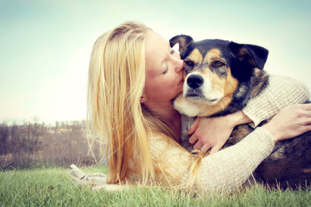 a young caucasian woman with long blonde hair is laying outside hugging and kissing her German Shepherd Dog   Vintage style color  photo