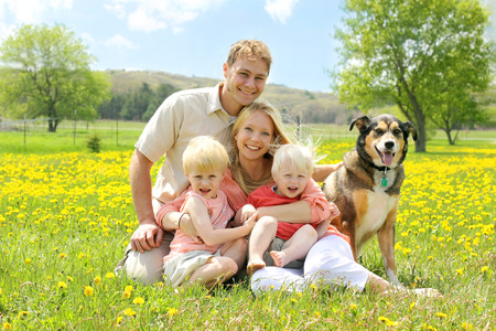 Portrait of a happy family of four people, including mother, father, young child, and baby sitting outside with their German Shepherd mix dog on a Spring day