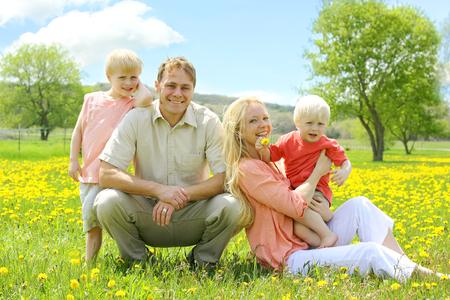 familia cristiana: Una familia feliz de cuatro personas, madre, padre, niño de corta edad, y su hermano pequeño está sentado en un prado de flores de diente de león en un día de primavera encantadora