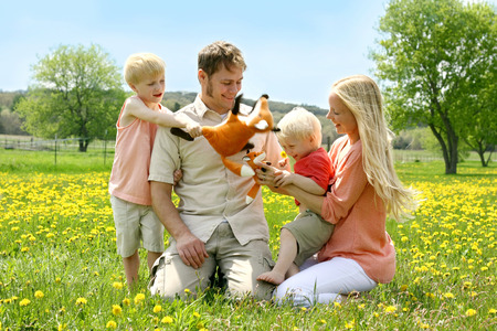 tickling: a happy family of four people, mother, father, young child and toddler, are playing with stuffed fox toys outside in a Dandelion flower meadow on a Spring day