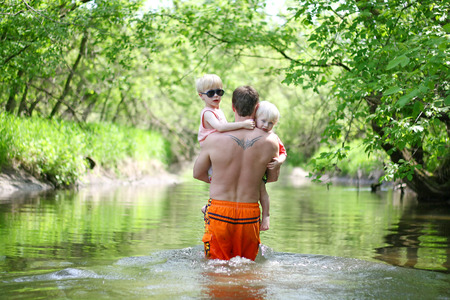 a father with a tattoo on his back is carrying his two young children outside through a river in the forest on a summer day