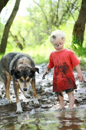 Un jeune enfant de garçon et de son chien de berger allemand mélange sont couverts de boue et jouer à l'extérieur sur la plage d'une rivière dans les bois Banque d'images - 28870921